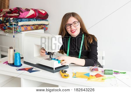 needlework and quilting in the workshop of a young woman - beautiful tailor woman sitting at a table with a sewing machine and thread, fabrics, needles, pins, buttons, she is looking away to a side