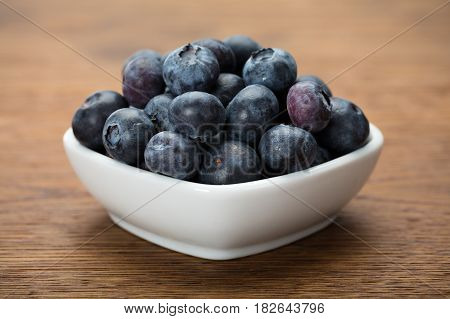 Heap Of Fresh Blueberries In White Bowl On Wood Table