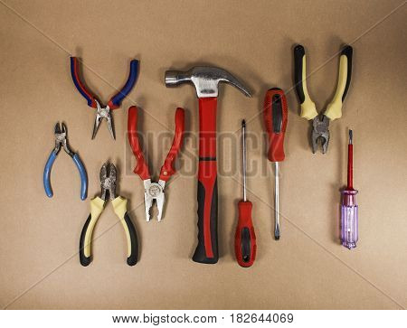 Many hand tools sorted on kraft background