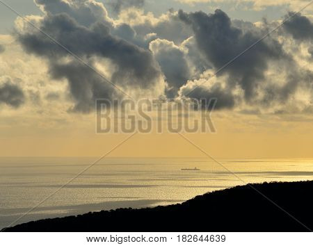Coastal landscape at dawn with scattered clouds over the sea