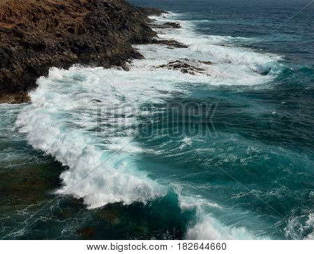 Littoral with groundswell and waves crashing against the rocks