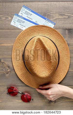 vacation concept with traveller outfit glasses, hat, tickets on wooden desk background top view