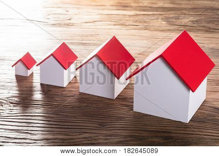 Increasing House Models With Red Roof In A Row On Wooden Table