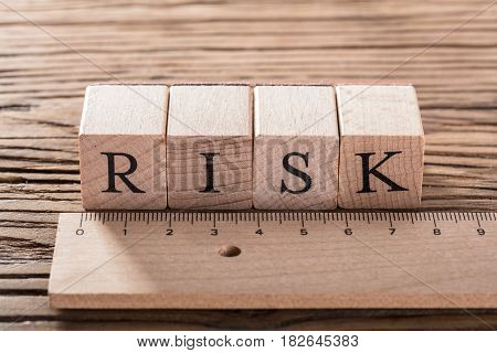 Risk Word On Blocks Arranged Behind The Ruler On Wooden Table