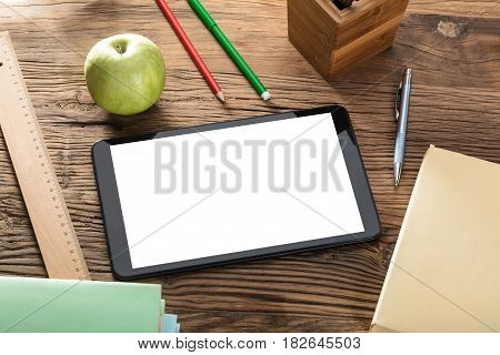 Green Apple And Blank Screen Digital Tablet On Wooden Table With Office Supplies