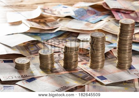 Increasing Coin Stacked On Euro Notes Over The Wooden Table