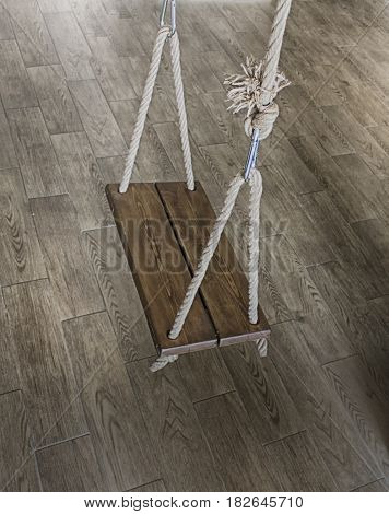Empty old wooden swing hanging at office