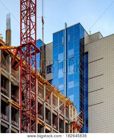 Crane and workers at construction of an office building against blue sky