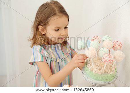 Cute little girl with tasty cake pops served for party