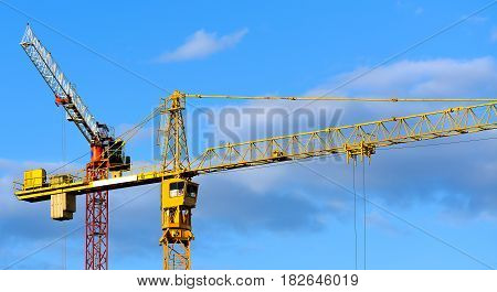 Construction Cranes against blue sky with clouds