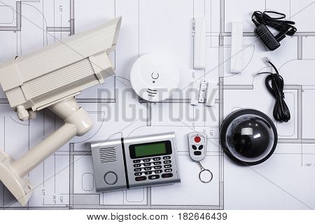 High Angle View Of Security Equipments On Blueprint In Office