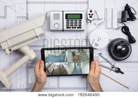 Close-up Of A Person Watching Footage On Digital Tablet With Security Equipments On Blueprint