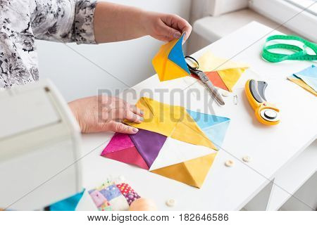needlework and quilting in the workshop of a woman tailor on white background - hands of tailor woman at work with pieces of colored fabric on the table with threads, fabrics, needles, cutters