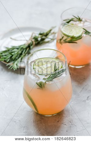 sliced lime, rosemary, plate and natural juice in glass on stone kitchen table background