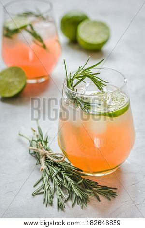 fitness cocktail in glass with cut lime and fresh rosemary on stone table background