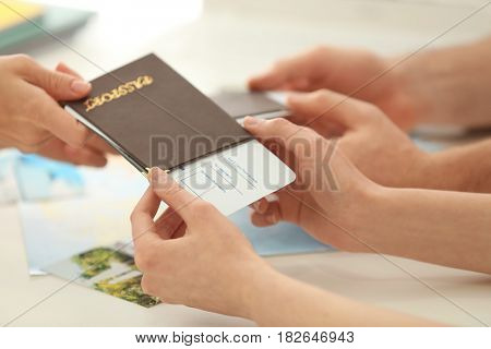 Adventure concept. Hands of young woman receiving passport with ticket at travel agency