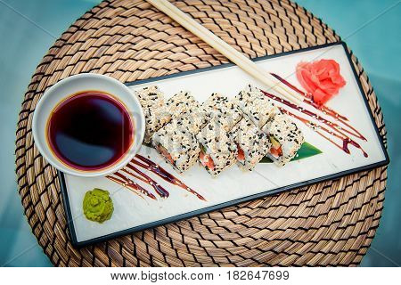 Rectangular plate with delicious rolls soy sauce ginger and wasabi on the table