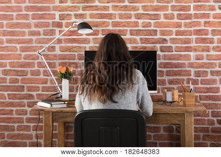 Rear View Of A Woman Using Computer