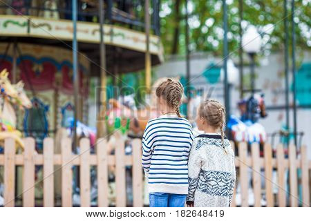 Little adorable girl on carousel at sunny day outdoor