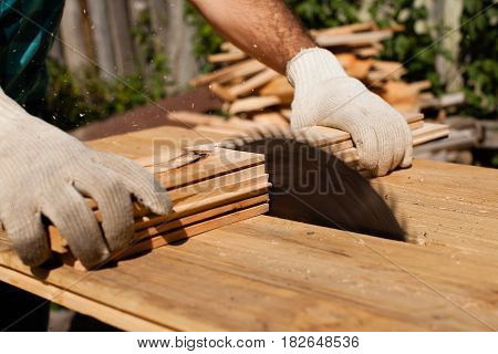 Hard working woodworker cutting wooden plank, focus on saw