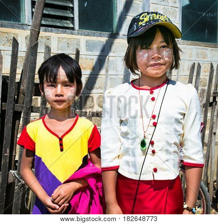NYAUNGSHWE, MYANMAR- MARCH 4, 2017: Childern with nature protection from the sun on face in the Nyaungshwe village on March 4, 2017 , Myanmar. (Burma)