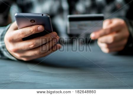 A man uses a mobile phone to pay for an internet application. Concepts of using mobile technologies and smarfon in mobile applications in the online business for payment with a credit card remotely