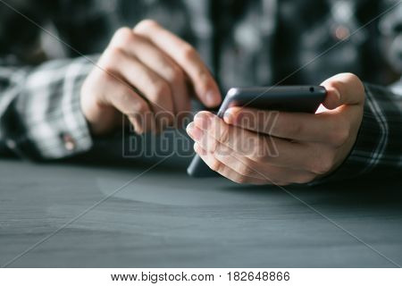 A man spends time in social networks with a mobile phone in his hands