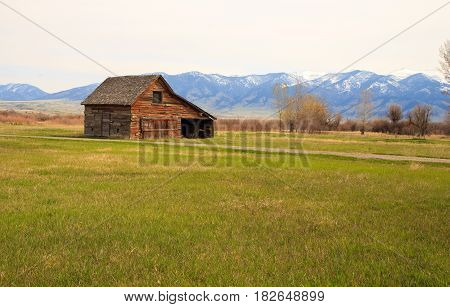 Landscape with a rustic vintage barn with mountains in background.