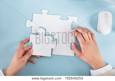 Elevated View Of A Businesswoman Joining The Jigsaw Puzzle Pieces On Blue Desk