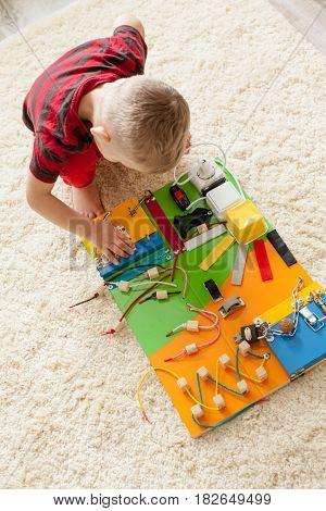 Handmade DIY sensory children's toy, three year's boy plays with busy board