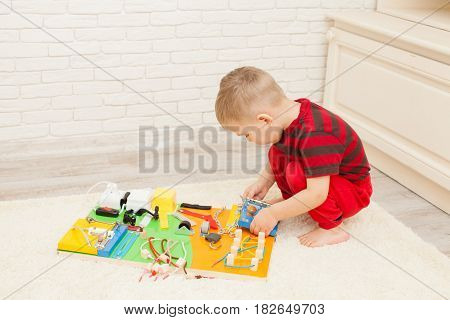 Handmade DIY sensory children's toy, three year's boy plays with busy board