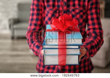 Woman holding stack of books with ribbon as gift on blurred background