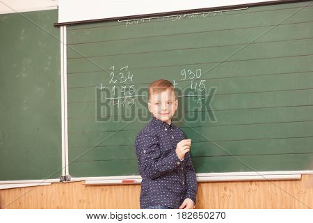 School boy solves examples at the board on the lesson in mathematics