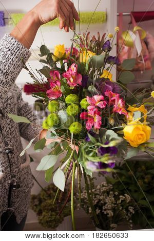 Florist making fashion bouquet of colorfull flowers