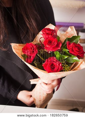 Florist making fashion bouquet of beautiful red roses