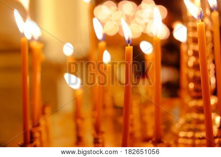 Charming lights of burning candles in church