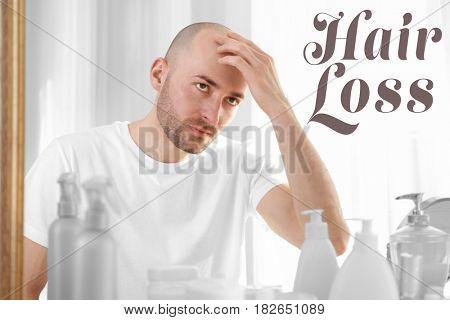 Hair loss concept. Man looking at mirror