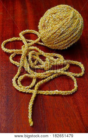 Yellow wool yarn skein on the red table