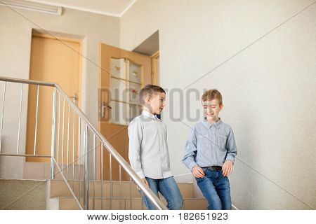 Two boys go downstairs and talking after the lesson in primary school