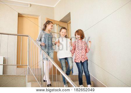 Three girls in the school hallway talking resting during the break