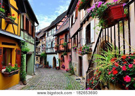 Quaint Colorful Cobblestone Lane In The Alsatian Town Of Eguisheim, France