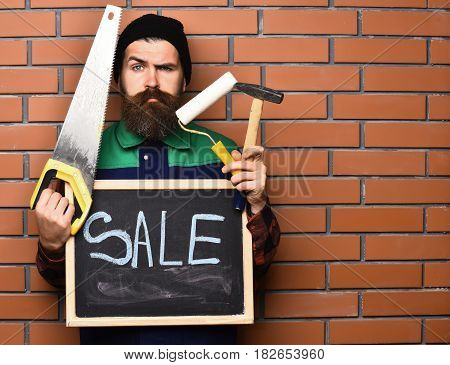 Bearded Man Holding Various Building Tools And Board, Serious Face