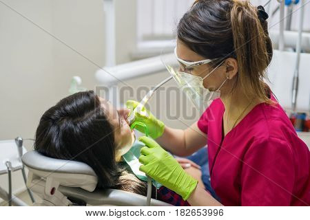 Female stomatologist treating woman's teeth in dental clinic