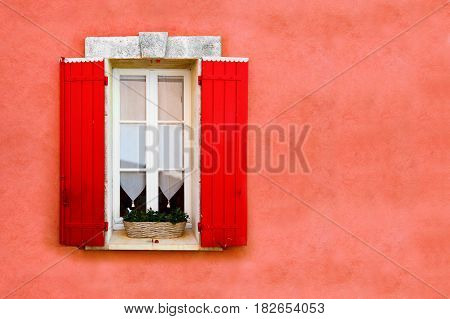 Red shuttered window against red ocher colored wall