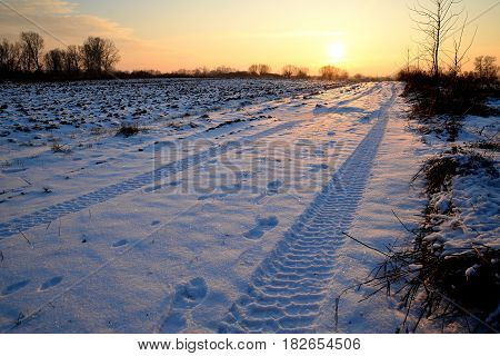 Winter wasteland with traces of tires on snow and sunset