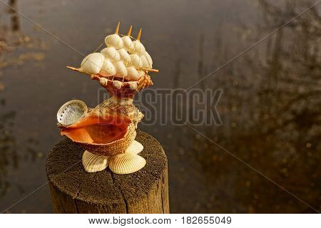 A mock ship from sea shells stands on a wooden pole