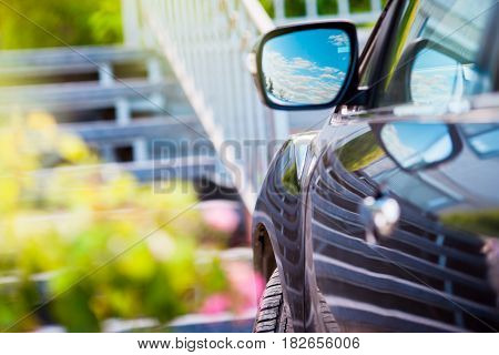 Reflection of sunny blue sky at the car side mirrow.