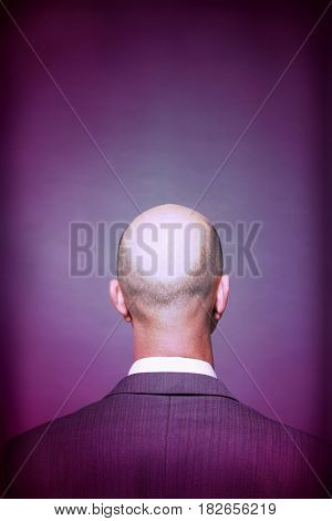 Rear view of a bald businessman against gray background