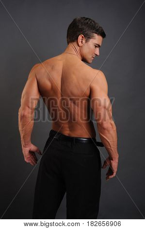 The beefcake muscle man is flexing his back.