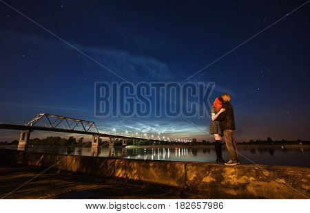 Loving people standing against a background of the night sky. The girl with red hair and a guy with long hair standing on the background of the river. Man and woman hugging. Bridge on the River. People on nature. People in night. People on dark background